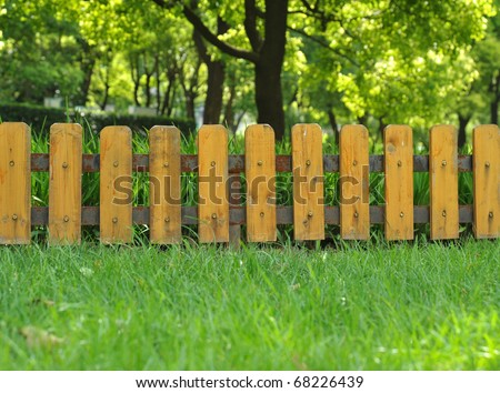 Wooden fence on green grass lawn