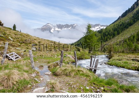 Wooden fence on mountain river in the Austrian Alps