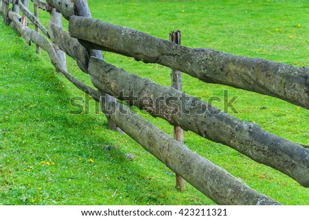 Wooden fence on nice green meadow - stock photo