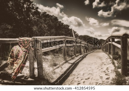 Wooden Fence on sandy pathway to beach grass and dunes at caprera sardinia - stock photo