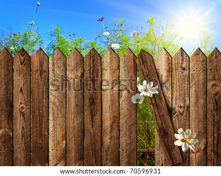 wooden fence over the courtyard with sky and sun - stock photo