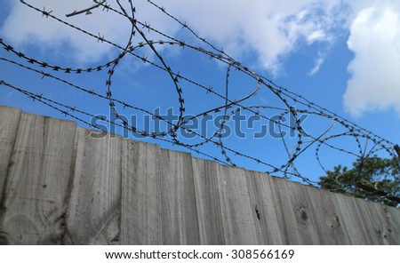 Wooden Fence with Barbed Wire - stock photo