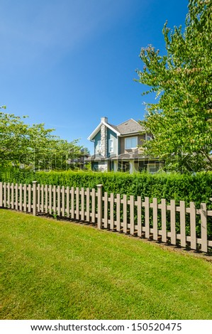 wooden fence with green lawn and trees - stock photo