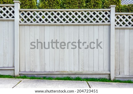Wooden fence with trees in the background. - stock photo