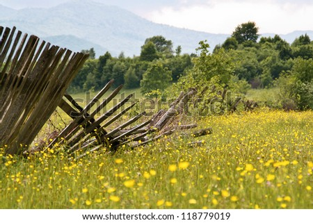 Wooden fences broken down in the grass - stock photo