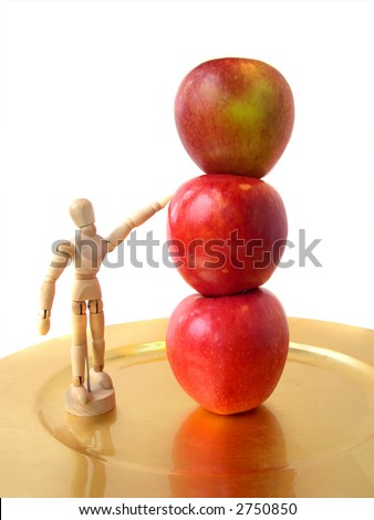 Wooden figure and three apples on gold plate