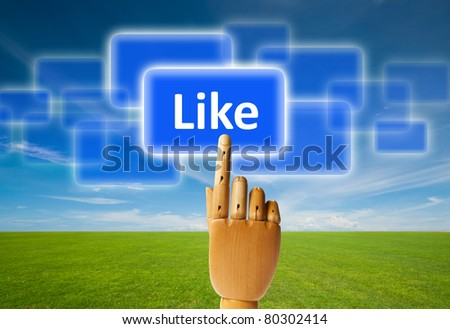 Wooden finger pressing a like button. - stock photo