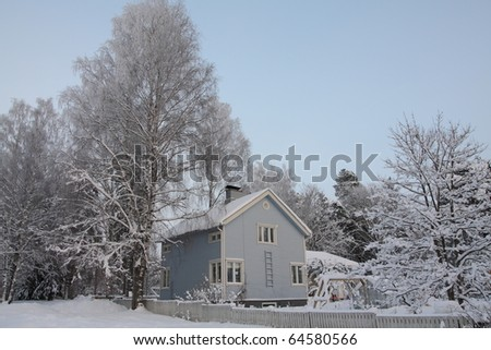 Wooden Finnish house in winter covered with snow - stock photo