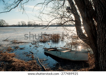 Wooden fishermanâ??s boat at the bank of Oka River in Russia at sunrise - stock photo
