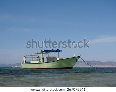 Wooden fishing boat anchored at the sea coast, Egypt - stock photo
