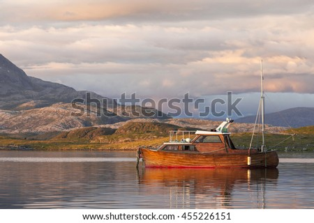 Wooden fishing boat at still sea at sunset. Photographed in Helgeland, Norway. - stock photo