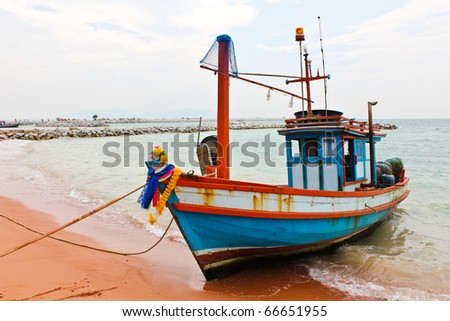 Wooden fishing boat on the beach. - stock photo