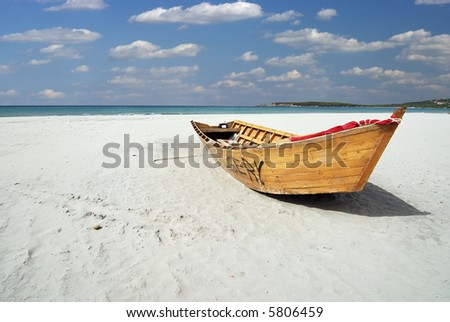 Wooden fishing boat on the white beach - stock photo