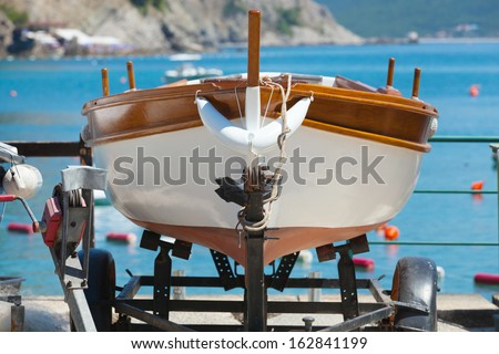 Wooden fishing boat stands on the coast of Adriatic sea. Petrovac, Montenegro - stock photo