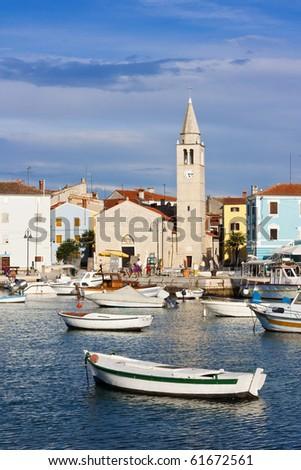 Wooden fishing boats and old stone church in harbor of Fazana in Croatia - stock photo