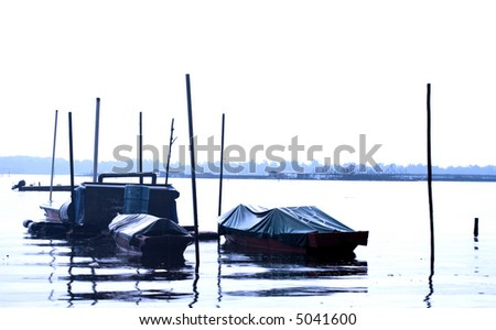 Wooden fishing boats moored by the jetty on a calm day