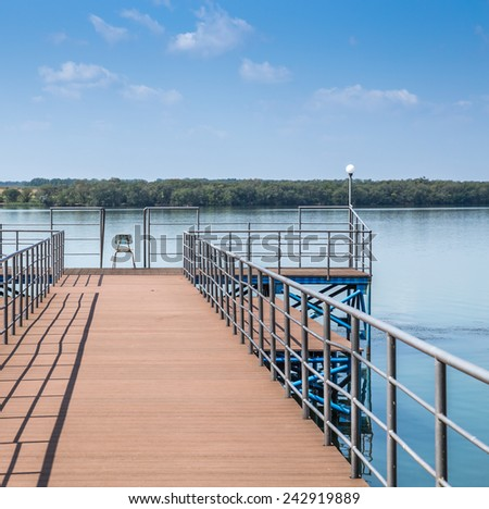 Wooden fishing pier on a beautiful lake with one chair in the middle - stock photo