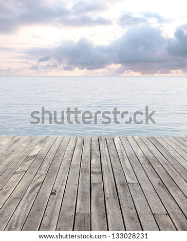 wooden floor and blue sea with waves and cloudy sky - stock photo