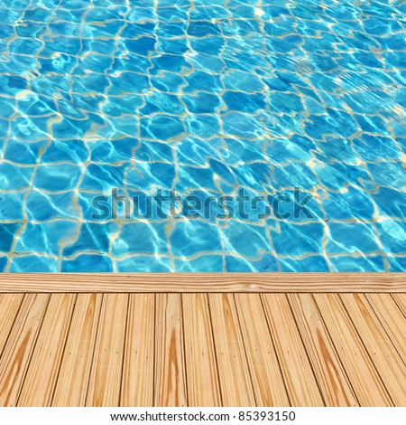 Wooden floor beside the blue swimming pool - stock photo