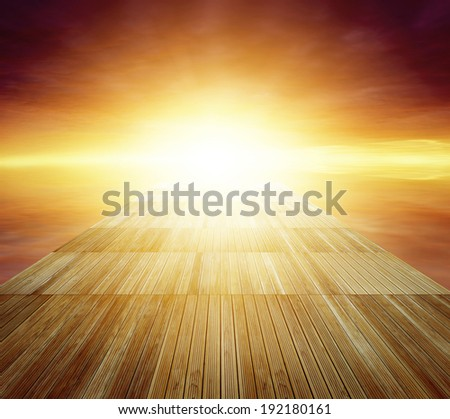 Wooden floor leading to bright sky - stock photo