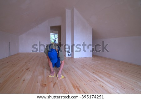 Wooden floor polishing, before varnished.Worker with emery. - stock photo