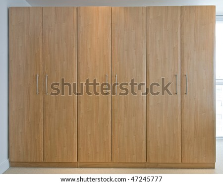Wooden floor to ceiling wardrobes - stock photo