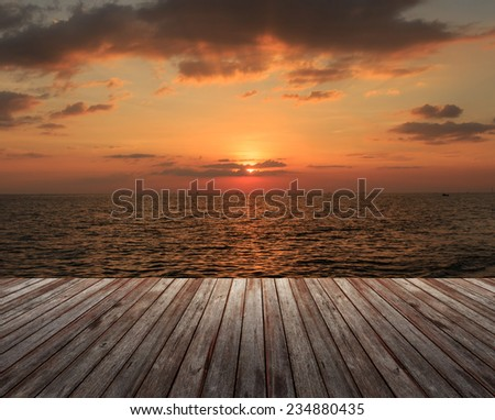 Wooden Floor under cloudy sky with sea at sunset - stock photo