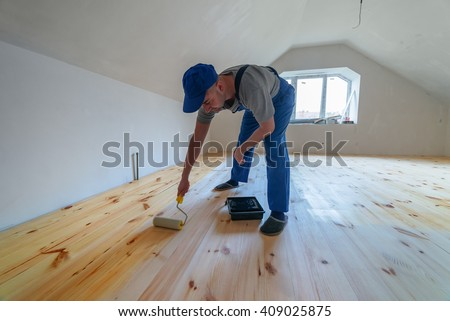 Wooden floor varnished. Worker with paint roller. - stock photo