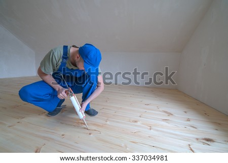 Wooden floor varnished. Worker with silicon gun. - stock photo