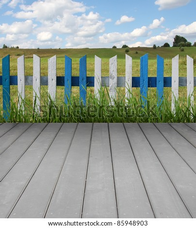 Wooden floor with fence, green grass and blue sky - stock photo