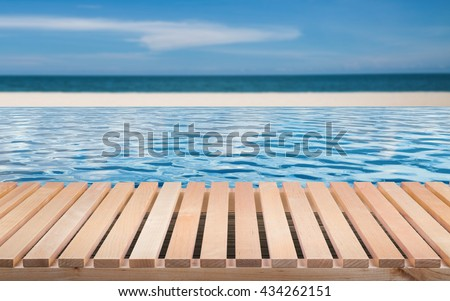 wooden floor with infinity pool on beach background - stock photo