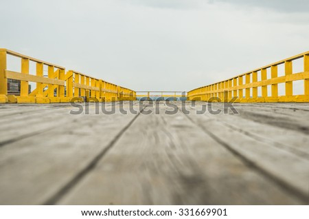 Wooden floor with yellow fence from natural material in sea with on gray and blue sky clouds. Outdoor background. No people, Empty copy space for object or inscription. Horizon in perspective. - stock photo