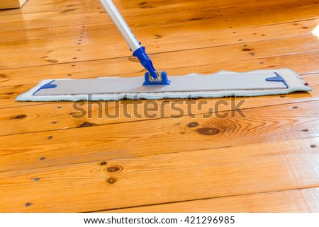 Wooden floors professional washing with mop in the room. Straight view on  the mop with handle on the wooden floor. Regular clean up. Maid cleans house. - stock photo