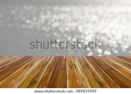 Wooden floors with a background bokeh of water in rivers or the sea. - stock photo