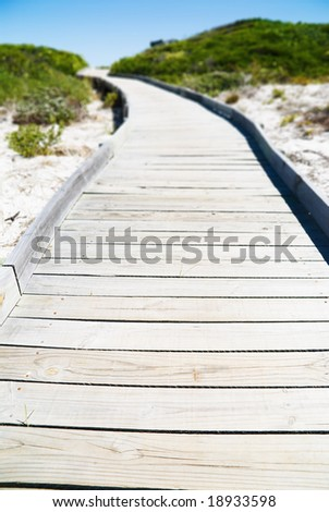 Wooden foot pathway through dunes - stock photo