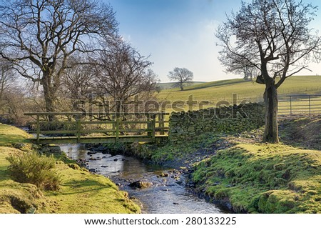 Wooden footbridge and ford crossing a small stream - stock photo
