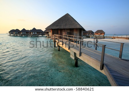 Wooden footbridge into the water bungalows at maldives - stock photo