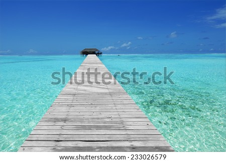 Wooden footbridge leading to overwater villa on the tropical green lagoon   - stock photo
