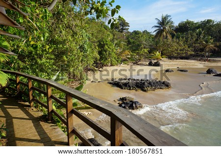 Wooden footbridge over a beautiful tropical beach with sand and rock, Bastimentos island, Red frog beach, Caribbean sea, Panama - stock photo