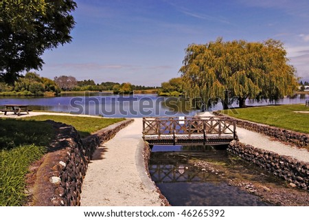 wooden footbridge over creek at park - stock photo