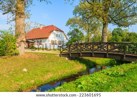 Wooden footbridge over small river and traditional cottage house in countryside landscape of Radziejowice village, Poland - stock photo