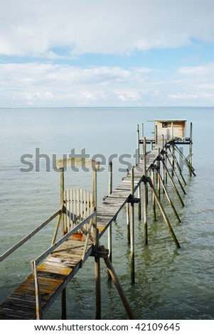 Wooden footbridge over the sea leading to a fishing hut.