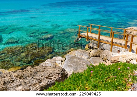 Wooden footbridge to crystal clear sea water on coast of Cyprus island near Protaras - stock photo