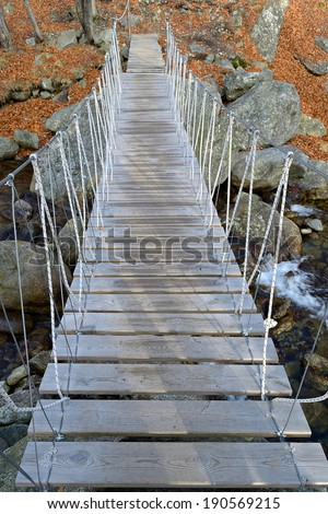 Wooden footbrigde suspended by steel ropes on mountain stream in tha italian Alps. - stock photo