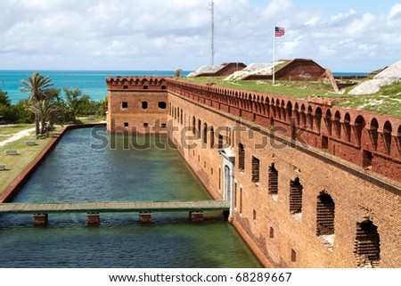 Wooden footpath crosses the moat and leads to the entrance of Fort Jefferson National Park in the Dry Tortugas. - stock photo