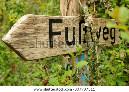 wooden footpath sign in the forrest written in german language - stock photo