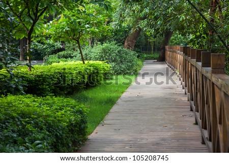 wooden footpath through a verdant garden - stock photo