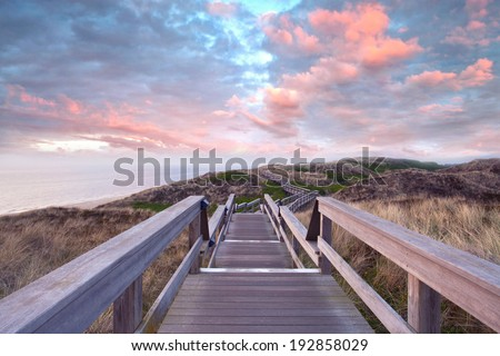 Wooden footpath through dunes at the North sea beach in Germany. sunset - stock photo