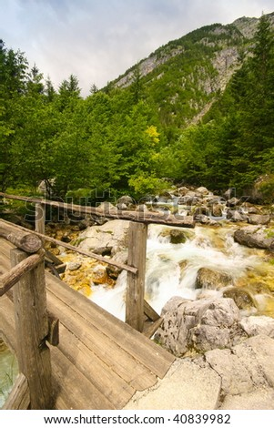 Wooden footpath with river and mountain in alps - stock photo
