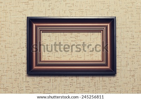 wooden frame on beige paper textured background - stock photo
